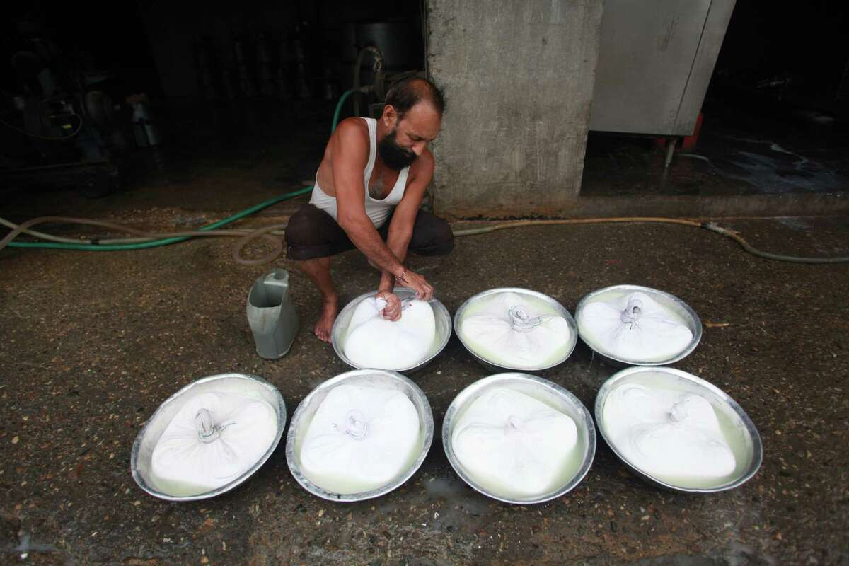 An Indian man prepares cottage cheese by the side of a road in Jammu, India.