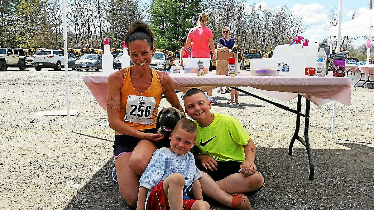 Girls Just Wanna Run 5K first-place winner Laura Pieger, 42, of Watertown pauses with sons Jackson, 4, Mason, 9, and Blue, their 12-week-old English Mastiff.