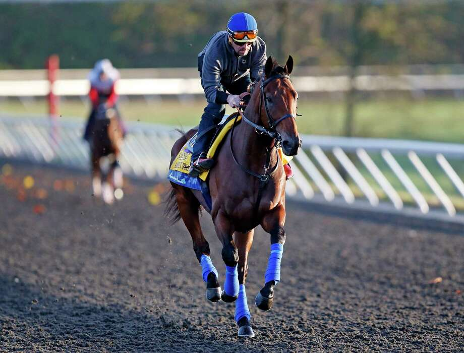 Triple Crown winner American Pharoah is ridden by exercise rider Jorge Alvarez during a workout for the Breeders' Cup Classic Thursday at Keeneland race track in Lexington, Ky. Photo: Brynn Anderson — The Associated Press  / AP