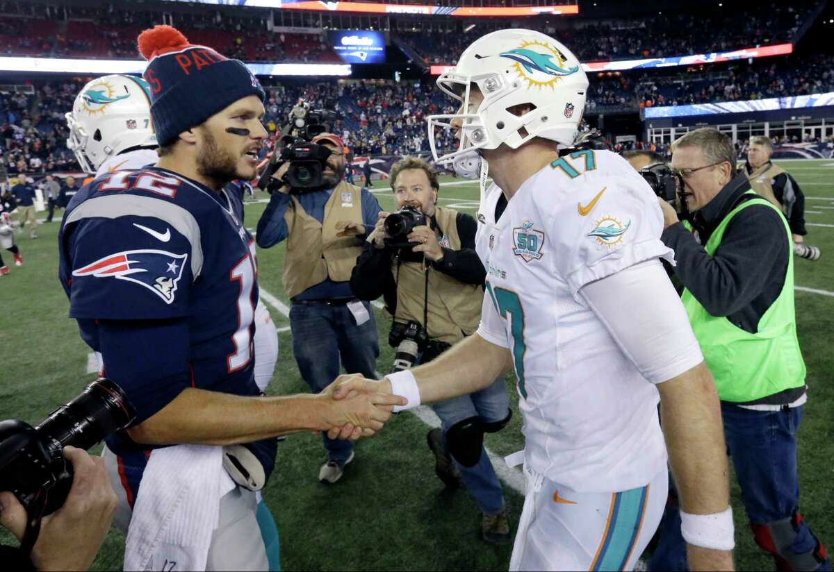 New England Patriots quarterback Tom Brady, left, shakes hands with Miami Dolphins quarterback Ryan Tannehill after Thursday's game in Foxborough, Mass.