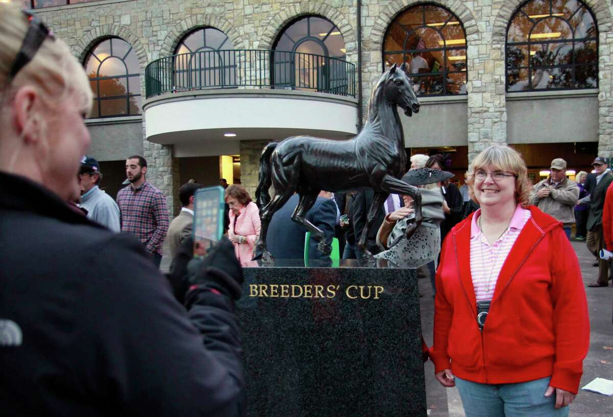 Kim Langston of Daphne, Ala., has her photo taken by a friend by a statue in the grandstand area at Keeneland.