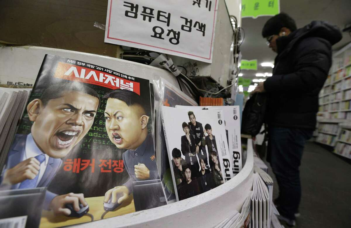 """A magazine with cartoons of U.S. President Barack Obama, left, and North Korean leader Kim Jong Un is displayed at a book store in Seoul, South Korea, Saturday, Jan. 3, 2015. The United States imposed new sanctions Friday on North Korean government officials and the country's defense industry for a cyberattack against Sony, insisting that Pyongyang was to blame despite lingering doubts by the cyber community. The red letters on the magazine read """" Hacker War."""" (AP Photo/Ahn Young-joon)"""