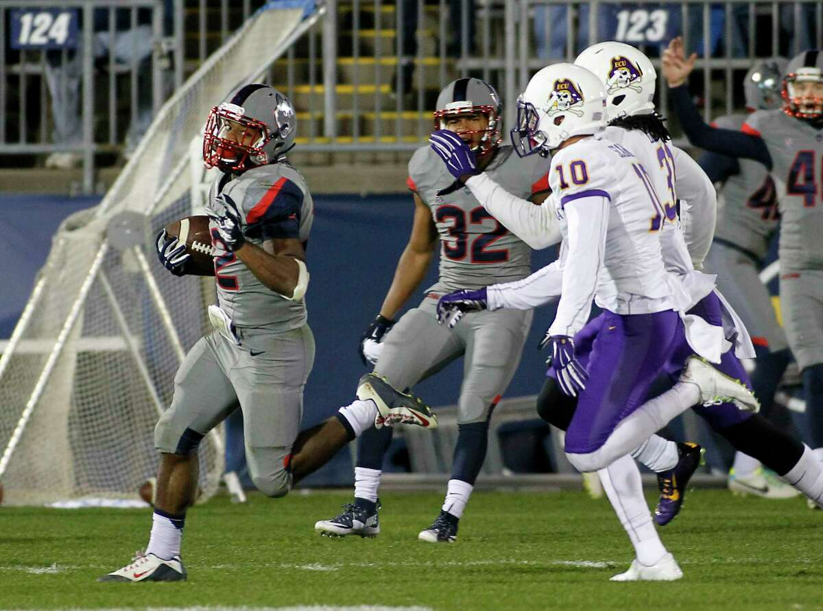 UConn running back Arkeel Newsome runs for a 90-yard touchdown as East Carolina's Rocco Scarfone (10) and Domonique Lennon pursue during the third quarter of the Huskies' 31-13 win on Friday in East Hartford.
