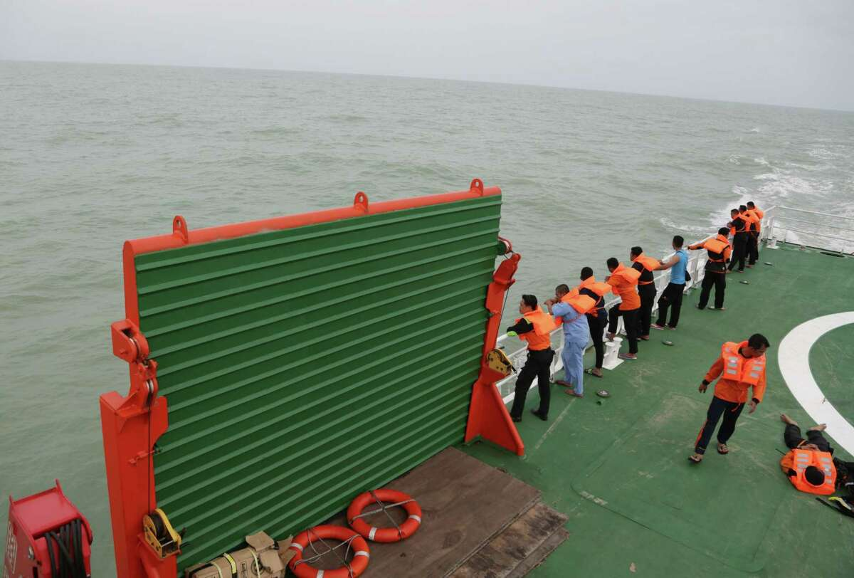 Members of the National Search And Rescue Agency (BASARNAS) stand on KN SAR Purworejo ship during a search operation for the victims of AirAsia flight QZ 8501 on the Java Sea, Indonesia, Saturday, Jan. 3, 2015. Indonesian officials were hopeful Saturday they were honing in on the wreckage of the ill-fated jetliner after sonar equipment detected large objects on the ocean floor, one week after the plane went down in stormy weather. (AP Photo/Achmad Ibrahim)