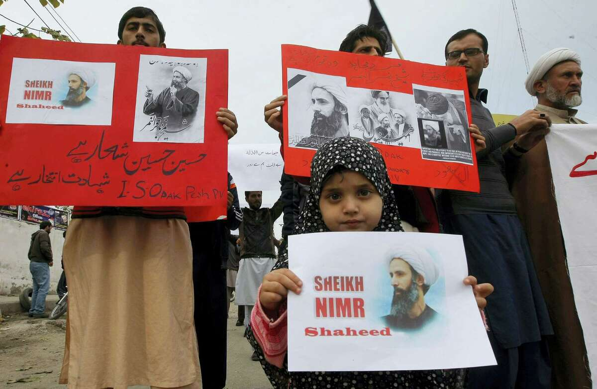 Shiite Muslims hold placards with pictures of Saudi Shiite cleric Sheikh Nimr al-Nimr, whose execution in Saudi Arabia was announced Saturday, during a demonstration to condemn his execution, Sunday, Jan. 3, 2016 in Peshawar, Pakistan. Saudi Arabia announced Saturday it had executed 47 prisoners convicted of terrorism charges, including al-Qaida detainees and al-Nimr, who rallied protests against the Saudi government. The placard on left reading as 'we for Hussein's way and martyrdom is a pride.'