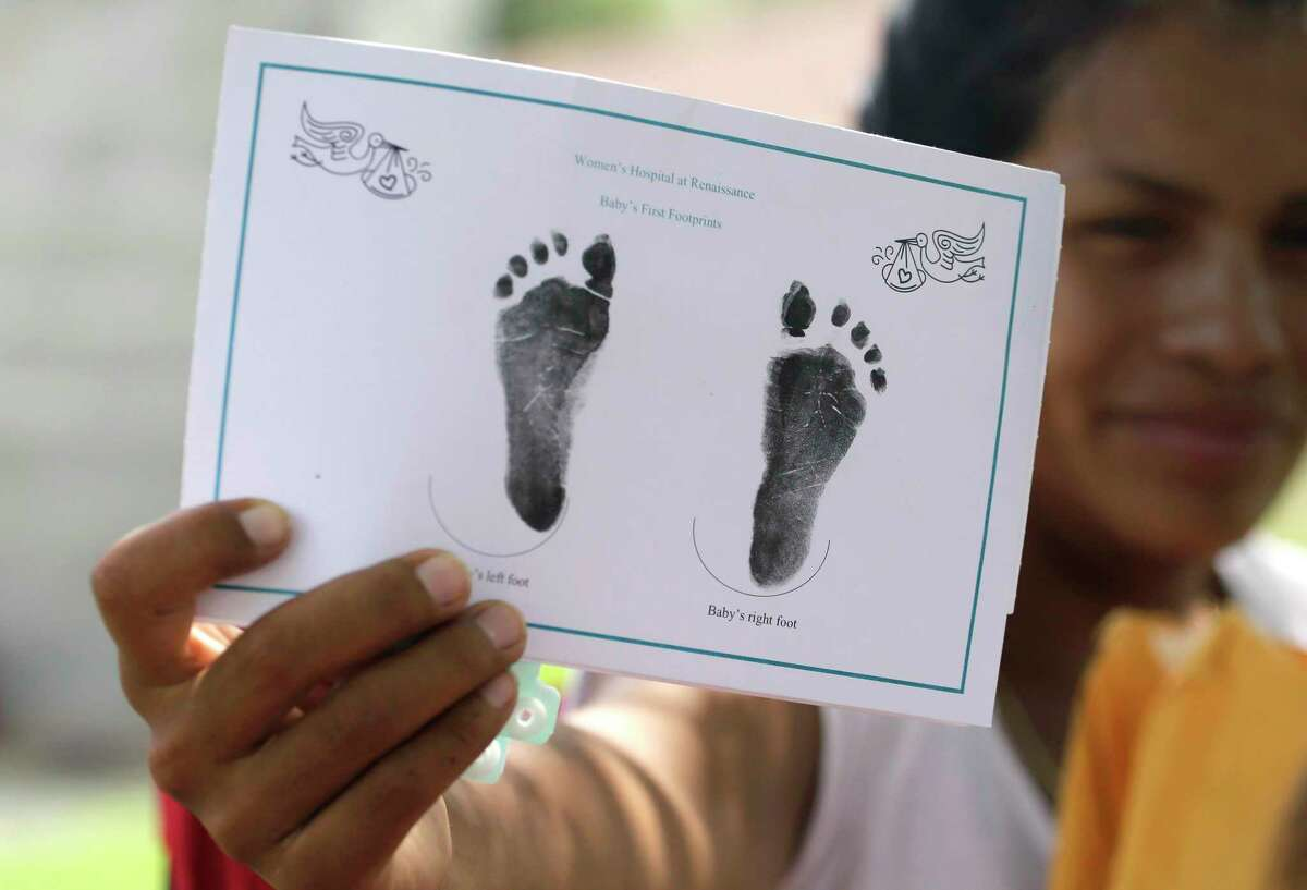 """In this Sept. 16, 2015, photo, a woman who said she entered the country illegally, shows in Sullivan City, Texas, the foot prints of her daughter who was born in the United State but was denied a birth certificate. A federal judge has chosen for now not to force Texas health officials to change their stance in denying birth certificates to immigrant families with U.S- born children, saying that the families raised """"grave concerns"""" but more evidence is needed, according to a ruling issued Friday, Oct. 16."""