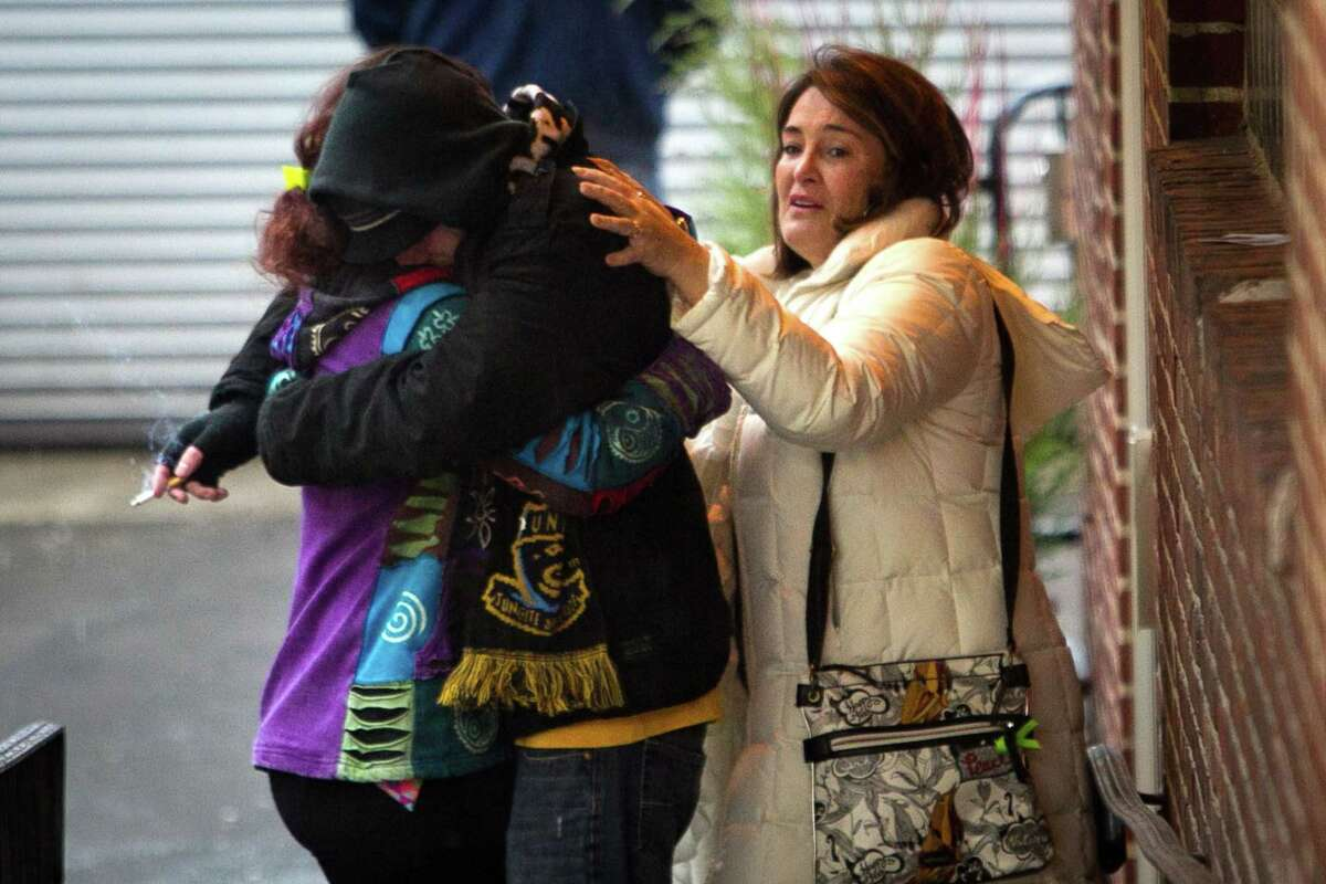 Unidentified people embrace in driveway to Manayunk Brewing Company near Shurs Lane on Saturday, Jan. 3, 2015. Earlier divers from Garden State Underwater Recovery Unit found the body of missing Philadelphian Shane Montgomery. Shane Montgomery has been missing since before Thanksgiving. (AP Photo/Philadelphia Daily News, Alejandro A. Alvarez)