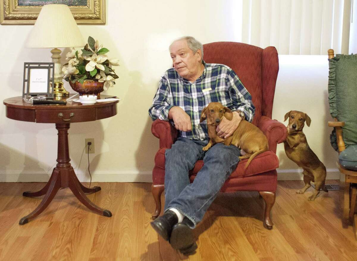 """Larry Wilkins retells the story of how his dogs, Bonnie and Pete (left), alerted him to a noise on his front porch, where he would meet the seven-year-old sole survivor of a airplane crash. """"I come to the door and there's a little girl, 7 years old, bloody nose, bloody arms, bloody legs, one sock, no shoes, crying,"""" Wilkins, 71, told The Associated Press on Saturday. """"She told me that her mom and dad were dead, and she had been in a plane crash, and the plane was upside down."""" (AP Photo/The Paducah Sun, John Paul Henry)"""