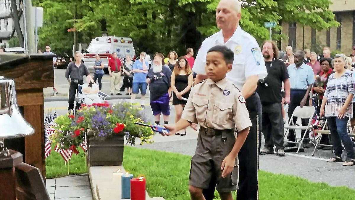 N.F. Ambery photo Boy Scouts of America's Troop 23 cub scout Patrick Sidharta, 11, lit candles at the Torrington Fire Department's remembrance ceremony.