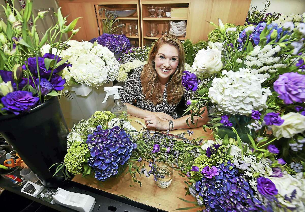 Catherine Avalone/New Haven Register Elise Samson, owner of Elise Floral, uses an assortment of hydrangea, lisianthus, limonium, statice, roses and eucalyptus to create a unique wedding arrangement.