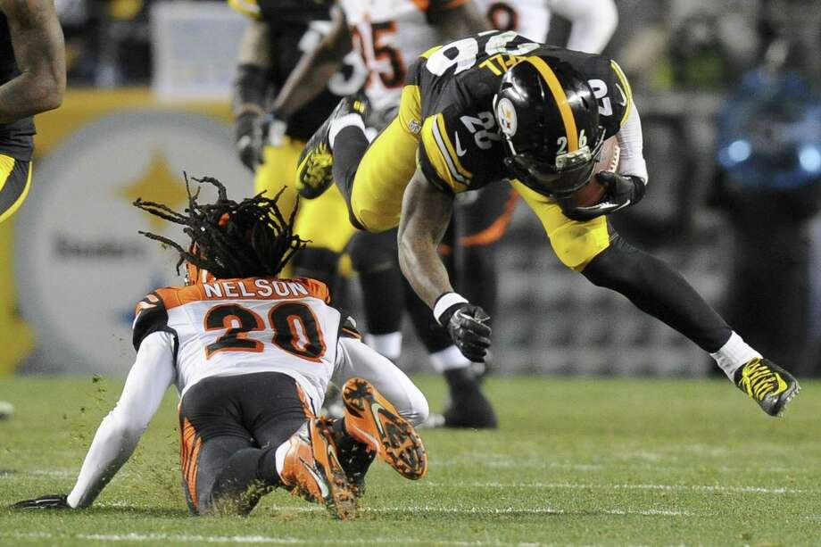Steelers running back Le'Veon Bell is hit by Cincinnati Bengals free safety Reggie Nelson during Sunday's game in Pittsburgh. Bell was injured on the play. Photo: Don Wright — The Associated Press  / FR87040 AP