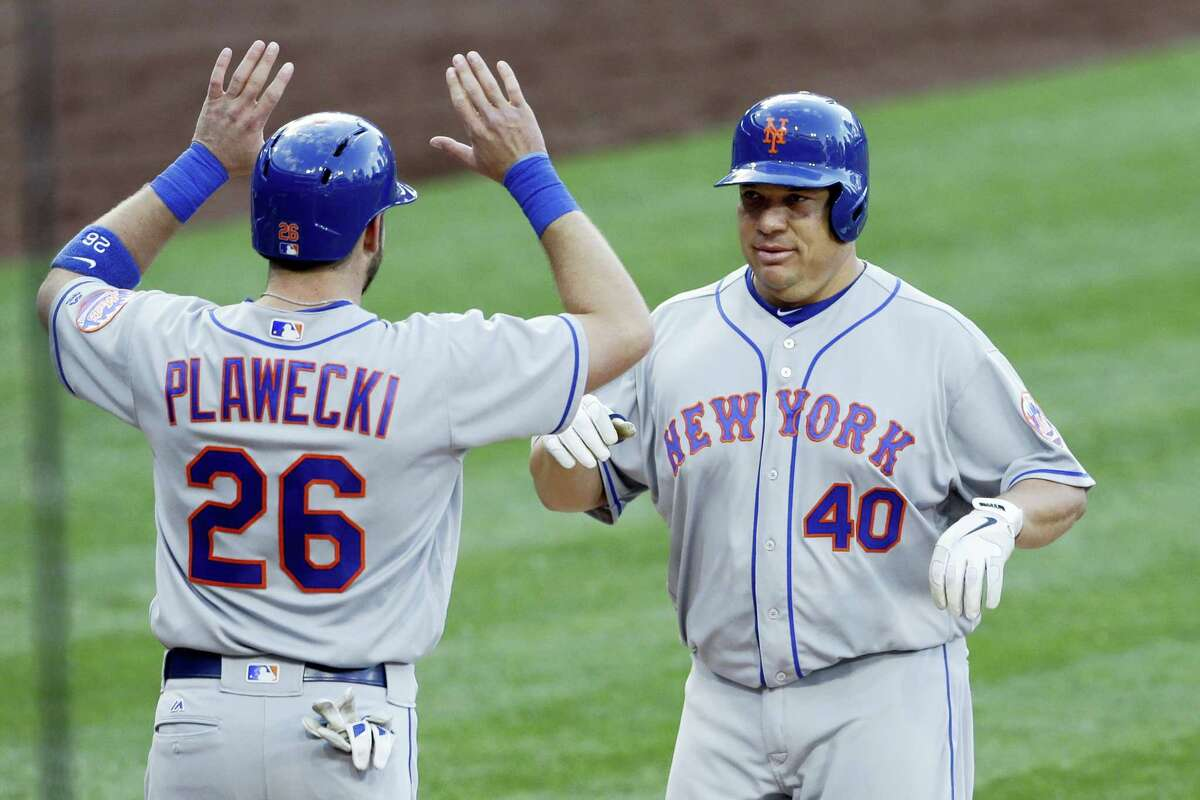 The Mets' Bartolo Colon, right, is greeted by teammate Kevin Plawecki (26) after hitting a two-run home run during the second inning on Saturday.