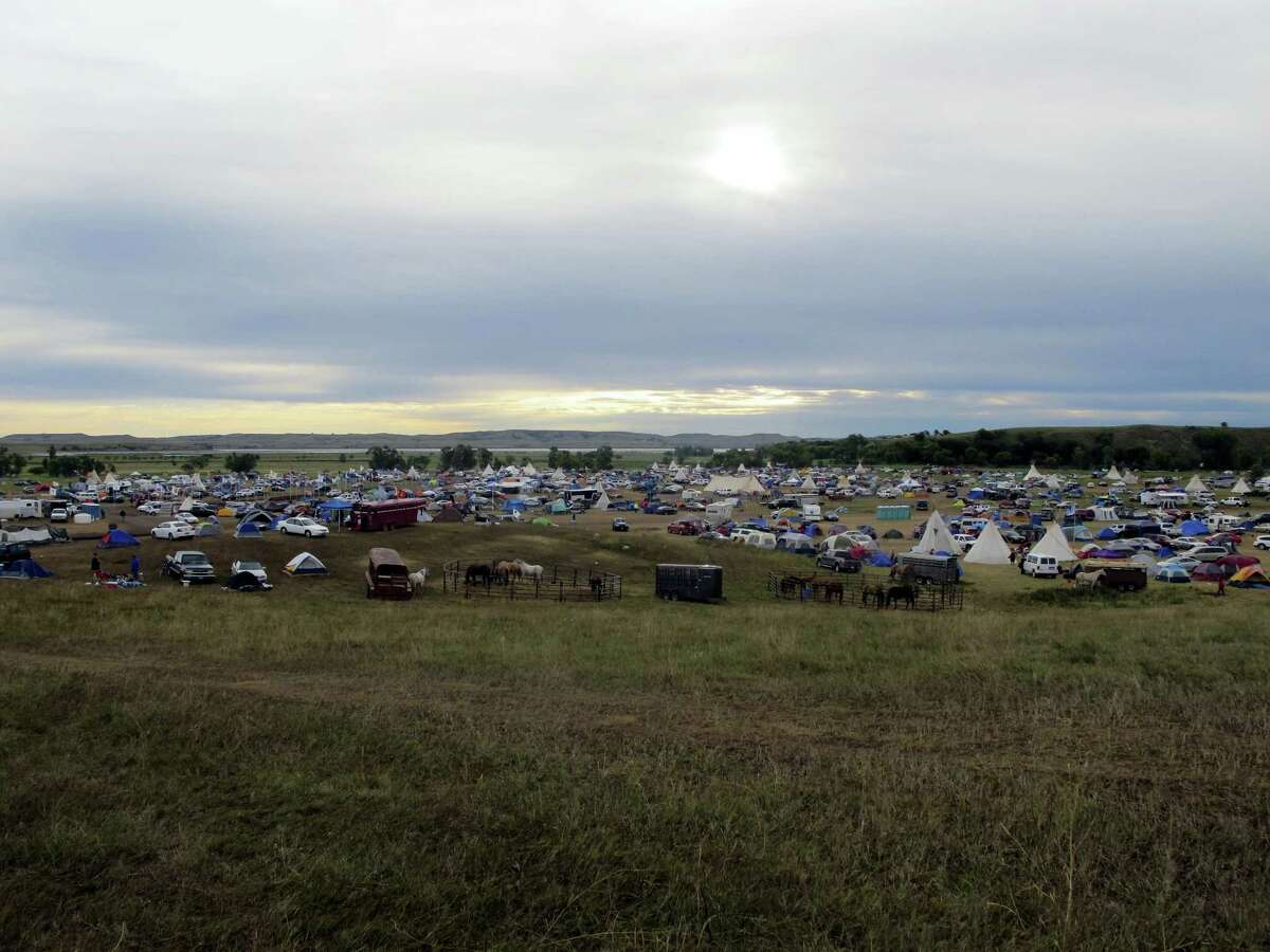 """More than a thousand people gather at an encampment near North Dakota's Standing Rock Sioux reservation on Friday, Sept. 9, 2016. The Standing Rock Sioux tribe's attempt to halt construction of an oil pipeline near its North Dakota reservation failed in federal court Friday, but three government agencies asked the pipeline company to """"voluntarily pause"""" work on a segment that tribal officials say holds sacred artifacts. (AP Photo/James MacPherson)"""