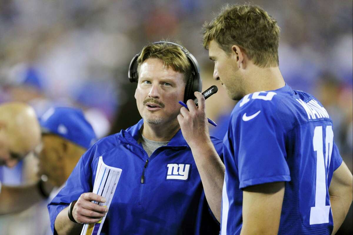 Giants coach Ben McAdoo, left, and talks with quarterback Eli Manning.