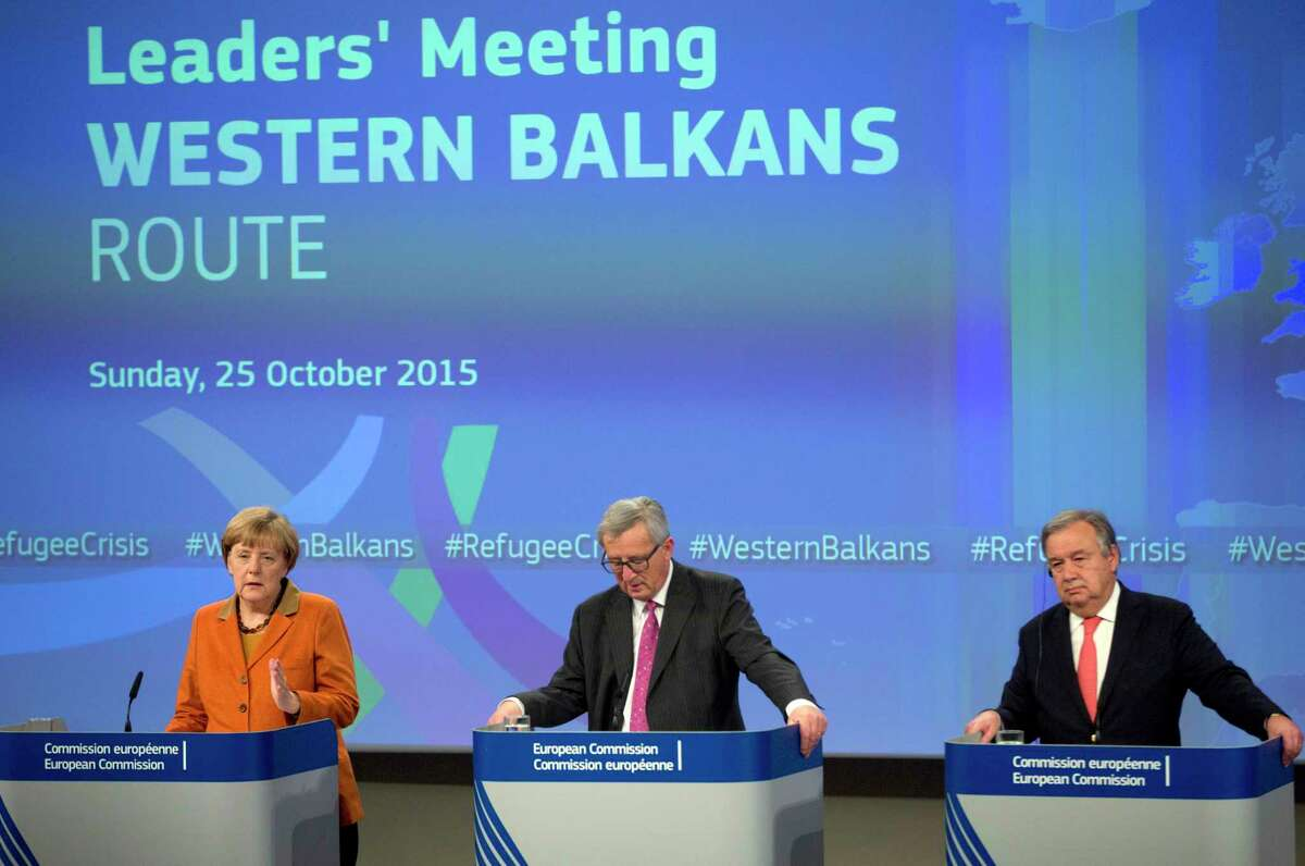 German Chancellor Angela Merkel, left, speaks during a media conference at the conclusion of an EU summit at EU headquarters in Brussels on Oct. 25. At center is European Commission President Jean-Claude Juncker and right is United Nation High Commissioner for Refugees Antonio Guterres.