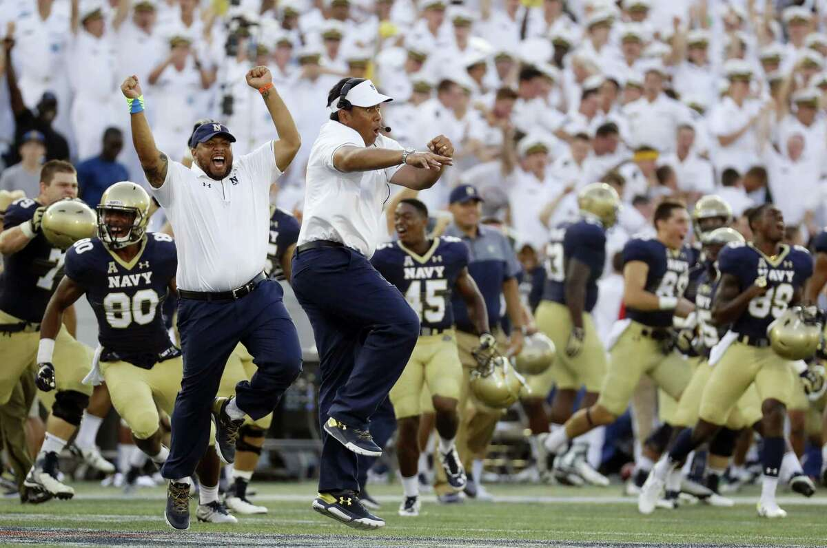 Navy head coach Ken Niumatalolo, center, celebrates after the Midshipmen beat UConn on Saturday.