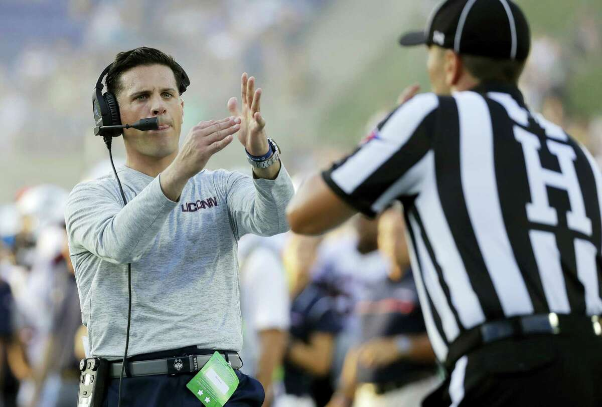 Connecticut head coach Bob Diaco, left, signals for a timeout to an official in the second half of an NCAA college football game against Navy in Annapolis, Md., Saturday, Sept. 10, 2016. Navy won 28-24. (AP Photo/Patrick Semansky)