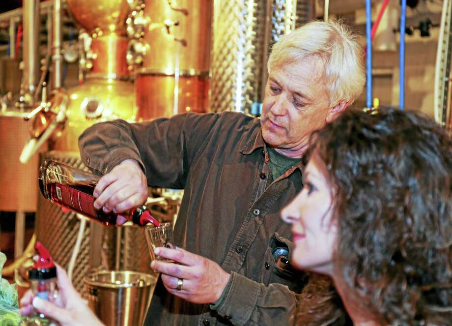 Jack Baker, partner at Litchfield Distillery, pours a sample. In foreground is Hilde Previs, sales ambassador for the distillery. Photo: Photo By John Fitts