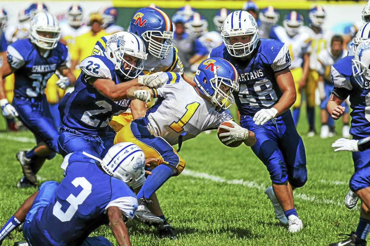 At 5-10, 155 pounds, G/N's Billy Komons gritted through two rushing touchdowns and a scoring interception return on a blistering hot day at Muzzy field.