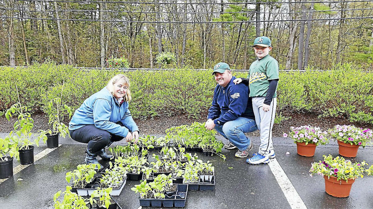 Barkhamsted Women's Club member Debbie Cloud assisted customers Michael Stapleton and his son Brayden, 9, both of Barkhamsted, at the Women's Club's 19th annual Mother's Day Flower Sale at the Barkhamsted Town Garage Saturday, May 7, 2016.