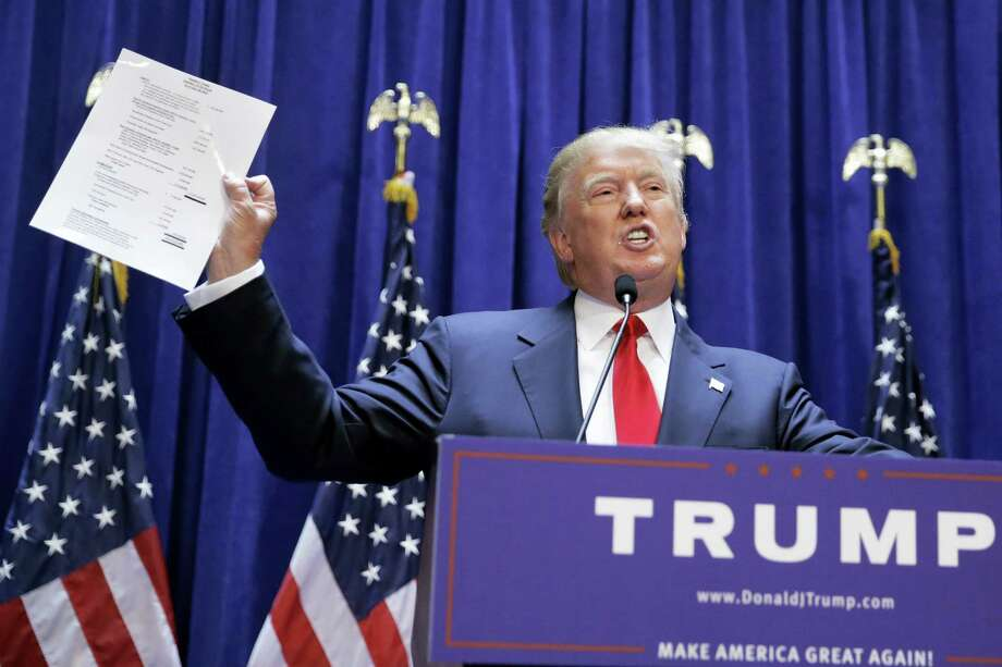 Developer Donald Trump displays a copy of his net worth during his announcement that he will seek the Republican nomination for president Photo: AP Photo — Richard Drew   / AP