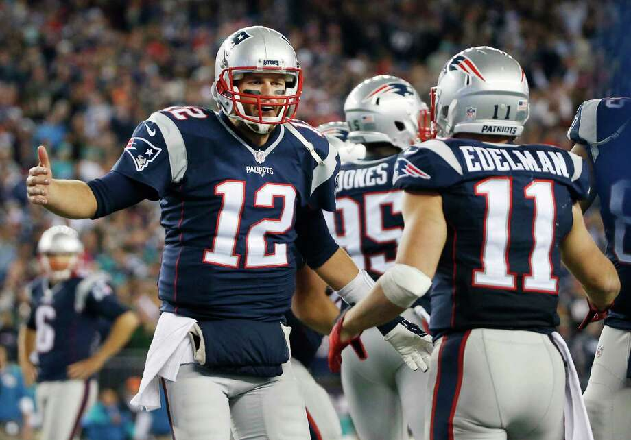 Patriots quarterback Tom Brady (12) celebrates his touchdown pass to wide receiver Julian Edelman in the second half against the Dolphins Thursday. Photo: Michael Dwyer — The Associated Press  / AP