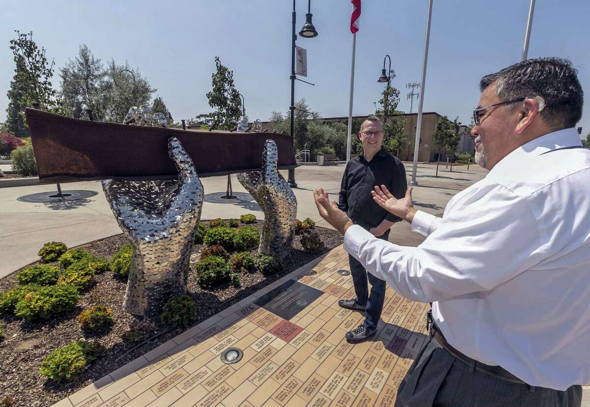 """In this Friday, Aug. 26, 2016, photo, California State EDD employee Juan Milan, right, talks with artist Heath Satow about his sculpture, """"Reflect,"""" made with a damaged, rusted I-beam from the collapsed World Trade Center buildings, outside the Rosemead, Calif., city hall plaza. Satow said he purposely positioned the beam at about eye level, so people could see, touch and feel it."""