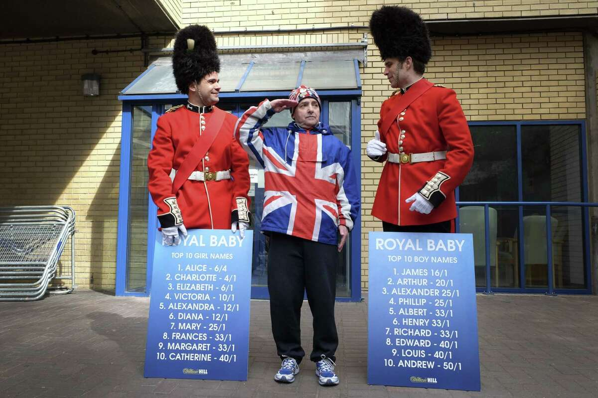 Royal supporter John Loughrey, centre, salutes as he stands with men dressed as soldiers carrying boards with proposed baby names on, outside the Lindo Wing of St Mary's Hospital in London, Friday, May 1, 2015. Kate, The Duchess of Cambridge is due to give birth at the hospital in the next few days. (AP Photo/Kirsty Wigglesworth)