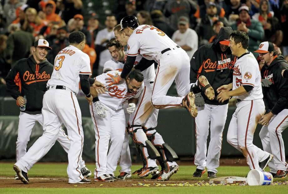 Members of the Baltimore Orioles celebrate with designated hitter Pedro Alvarez, third from left, after he hit a sacrifice fly ball in the 10th inning to defeat the Yankees 1-0 Photo: Patrick Semansky — The Associated Press  / AP