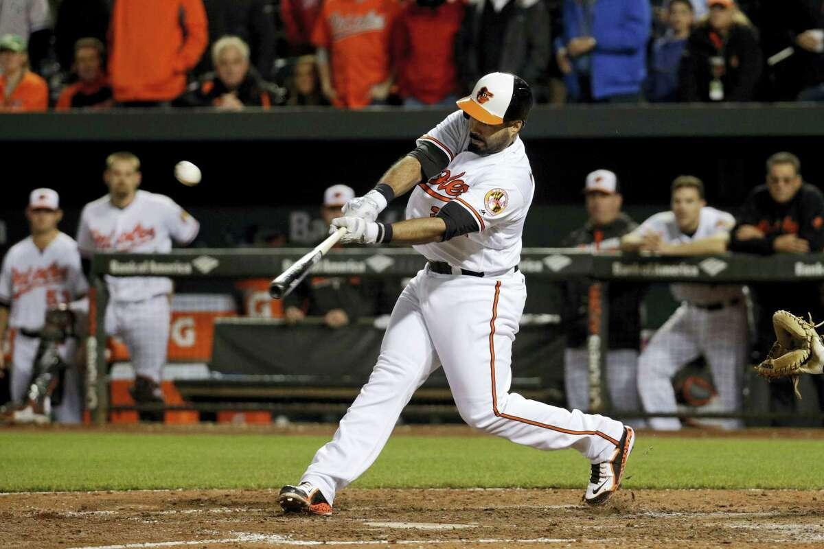 Baltimore Orioles designated hitter Pedro Alvarez hits a sacrifice fly ball in the 10th inning.