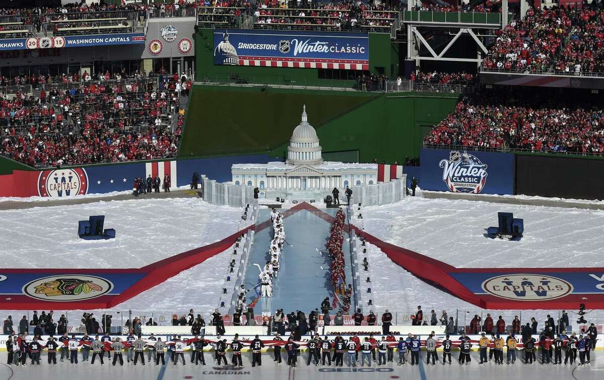 Chicago Blackhawks and Washington Capitals players line up for the national anthem before the start of the Winter Classic on Thursday at Nationals Park in Washington.