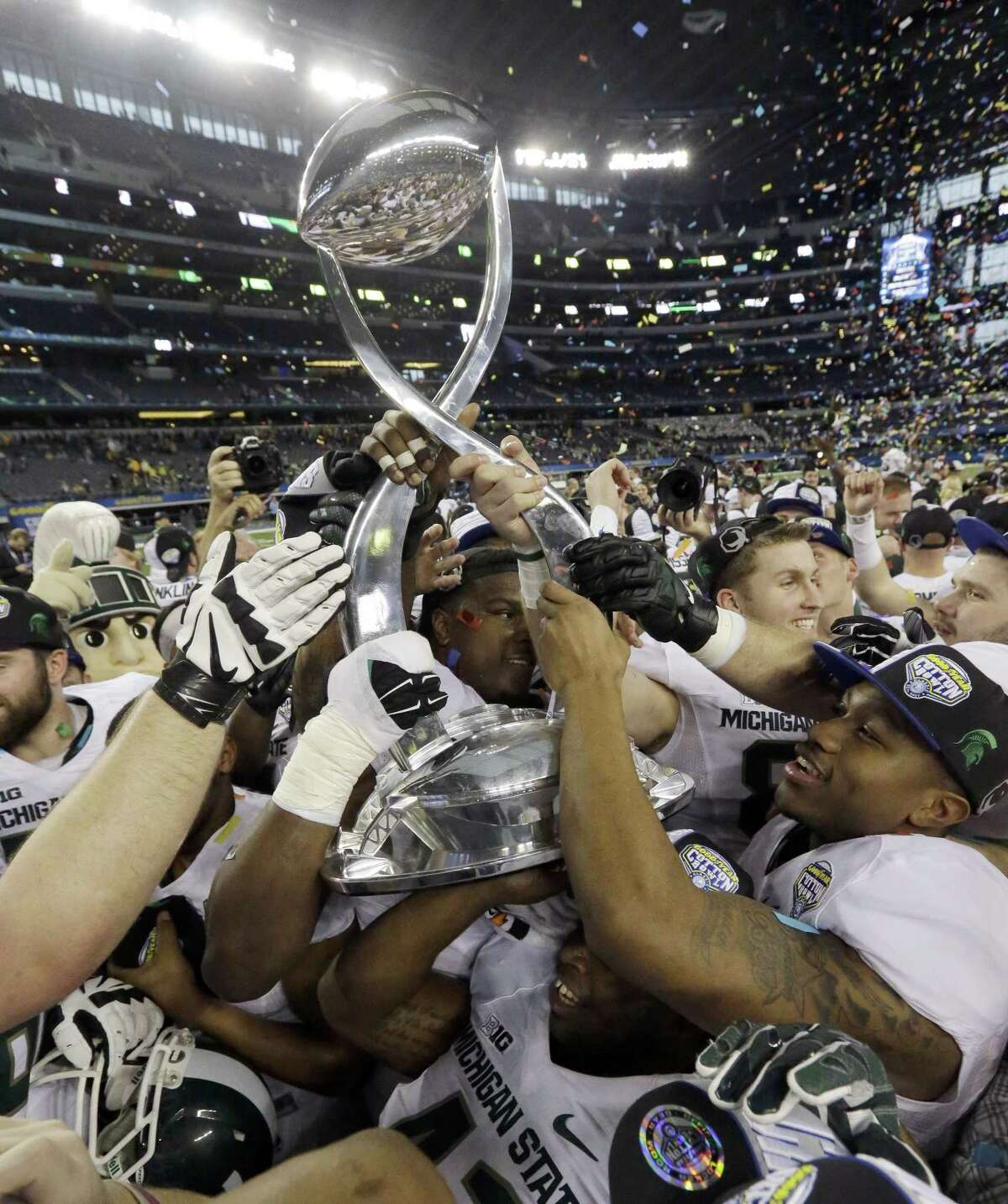Michigan State players hoist the trophy after they beat Baylor 42-41 in the Cotton Bowl on Thursday in Arlington, Texas.
