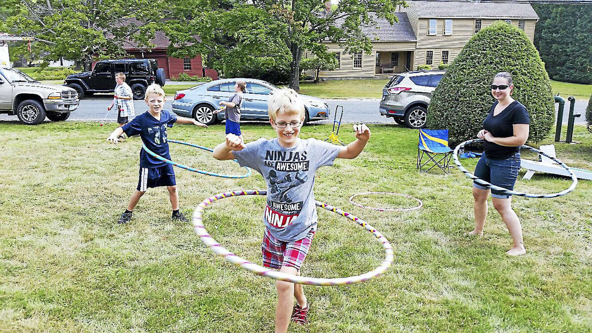 Jim Maloy, 7; his brother Jonas Maloy, 9; and Christine Rhodes, a volunteer with the Winchester Center Congregational Church, practiced their hula-hooping skills along with other lawn games during the fifth annual Winchester Center Day on Saturday. The event attracted about 500 people and featured draft horse-and-buggy rides; food vendors; interactive firefighting activities; live music; and sales of art, books, and crafts at the nearby Winchester Grange Hall.