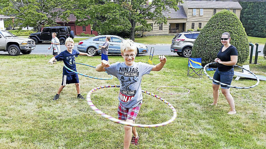 Jim Maloy, 7; his brother Jonas Maloy, 9; and Christine Rhodes, a volunteer with the Winchester Center Congregational Church, practiced their hula-hooping skills along with other lawn games during the fifth annual Winchester Center Day on Saturday. The event attracted about 500 people and featured draft horse-and-buggy rides; food vendors; interactive firefighting activities; live music; and sales of art, books, and crafts at the nearby Winchester Grange Hall. Photo: N.F. Ambery — The Register Citizen