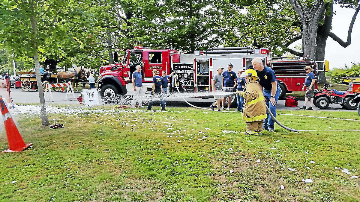 Jim Maloy, 7, learned from Todd Parsons, lieutenant of the Winchester Volunteer Fire Department, how to use a firefighter's water hose during the fifth annual Winchester Center Day on Saturday.