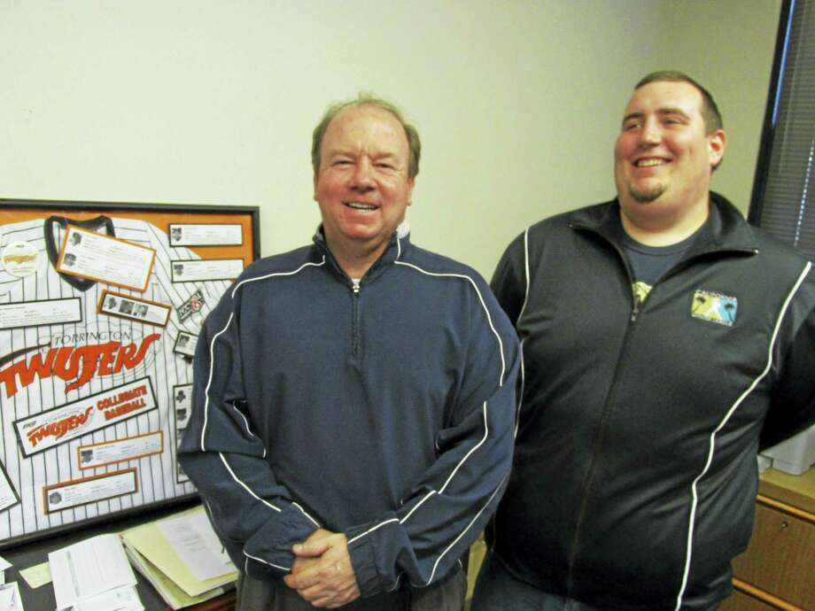 Titans General Manager Chris Myslow (left) and Assistant GM Dan Knapinski stand next to a throw-back display from Torrington's first collegiate baseball team, the Twisters. Photo: Photo By Peter Wallace