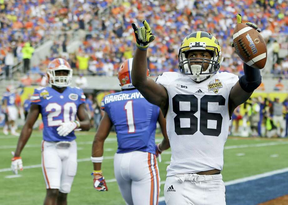 Michigan wide receiver Jehu Chesson celebrates his 31-yard touchdown reception as Florida defensive backs Vernon Hargreaves III (1) and Marcus Maye (20) walk off the field during the Citrus Bowl on Friday in Orlando, Fla. Photo: John Raoux — The Associated Press  / AP