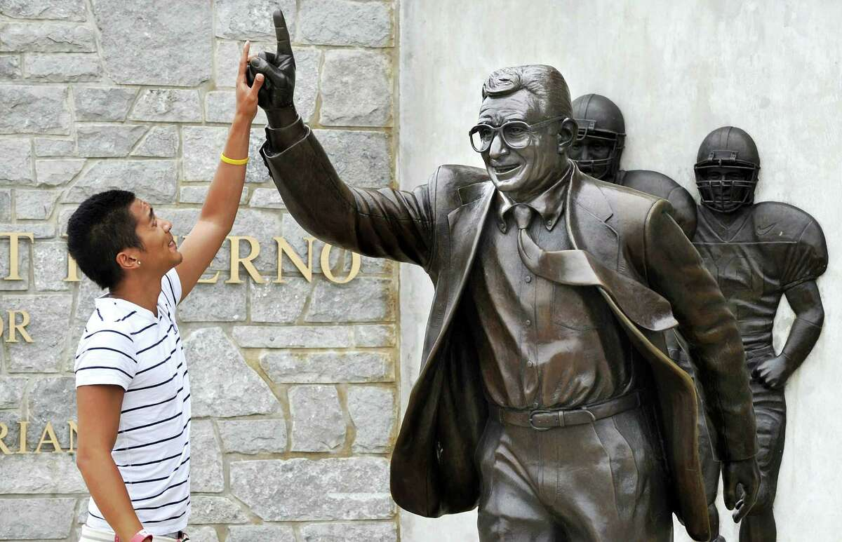 In this 2013 file photo, Joseph Jacobo, a senior at Penn State University, places his hand on the hand of the statue of Joe Paterno.