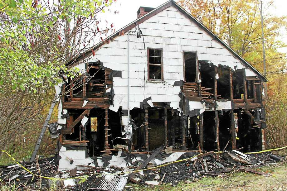 The origin of the fire that destroyed this vacant building located at 36 Boyd St. in Winsted remains under investigation. Two firefighters sustained minor injuries. Photo: Manon L. Mirabelli — The Register Citizen