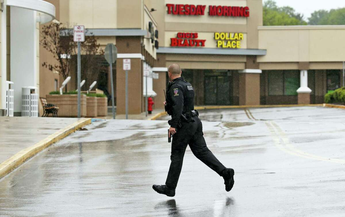 A police officer with his gun drawn runs for cover as Eulalio Tordil, 62, a suspect in three fatal shootings in the Washington, D.C., area is taken into custody nearby, in Silver Spring, Md., Friday, May 6, 2016. Tordil is an employee of the Federal Protective Service, which provides security at federal properties. He was put on administrative duties in March after a protective order was issued against him.