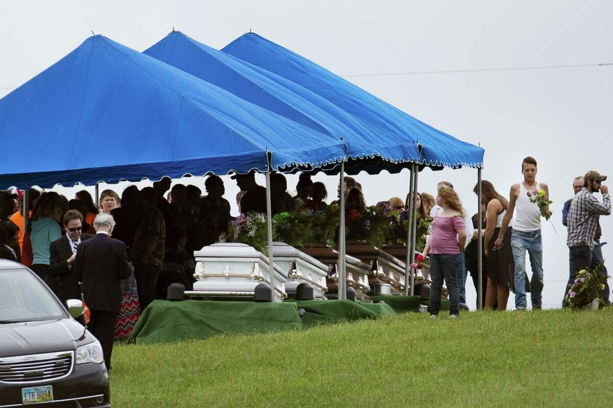 Mourners gather around row of caskets at Scioto Burial Park during funeral services for six of the eight murder victims from Pike County, Tuesday, May 3, 2016, in McDermott, Ohio. Seven adults and a 16-year-old boy from the Rhoden family were found dead April 22 at four properties scattered across a few miles of countryside near Piketon, about 80 miles east of Cincinnati.