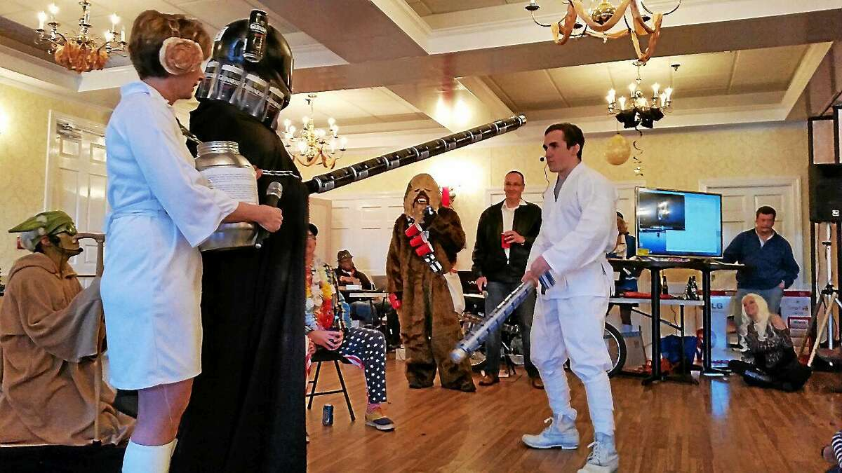 """A Guinness-beer-can-decorated Darth Vader prepares to combat Luke At-the-End-of-the-Bar-Talker (Ethan Pratt of Goshen) during a beer-themed spoof of """"Star Wars."""" at the 25th annual Possum Queen event in Litchfield Thursday."""