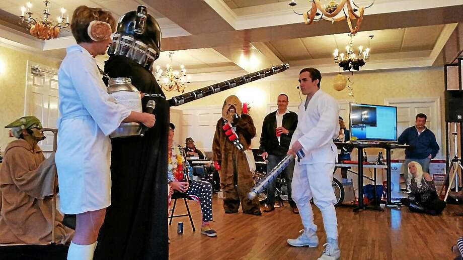 "A Guinness-beer-can-decorated Darth Vader prepares to combat Luke At-the-End-of-the-Bar-Talker (Ethan Pratt of Goshen) during a beer-themed spoof of ""Star Wars."" at the 25th annual Possum Queen event in Litchfield Thursday. Photo: (N.F. Ambery — The Register Citizen)"