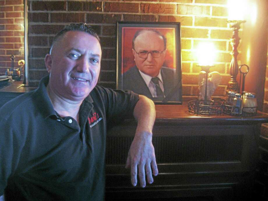 The owner, Bachi Prevalla, posing next to a picture of his father, the late Shaban Prevalla. Photo: Photo By John Torsiello
