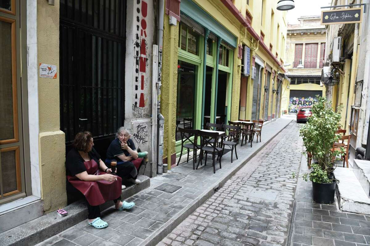 Employees of a restaurant talk on an empty street in the northern Greek port city of Thessaloniki, Tuesday. Greek Finance Minister Yanis Varoufakis confirmed that the country will not make its payment due later to the International Monetary Fund. Capital controls began Monday and will last at least a week, an attempt to keep the banks from collapsing in the face of a nationwide bank run.