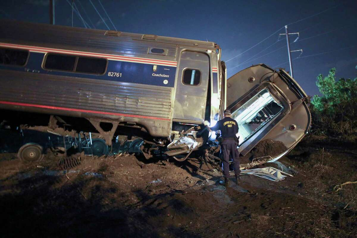 In this May 12, 2015, file photo, emergency personnel work the scene of a deadly train wreck in Philadelphia. The House has passed a bill delaying for three to five years the mandate for railroads to put long-sought safety technology in place. Federal accident investigators say the technology, known as positive train control, would have prevented a deadly Amtrak derailment in Philadelphia last May.