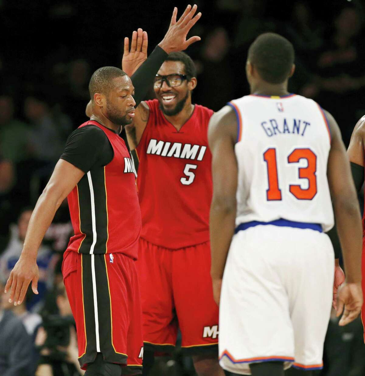 Miami Heat forward Amar'e Stoudemire (5) and guard Dwyane Wade (3) celebrate in the fourth quarter against the New York Knicks as Knicks guard Jerian Grant (13) watches during the Heat's 98-81 victory over the Knicks at Madison Square Garden Sunday.