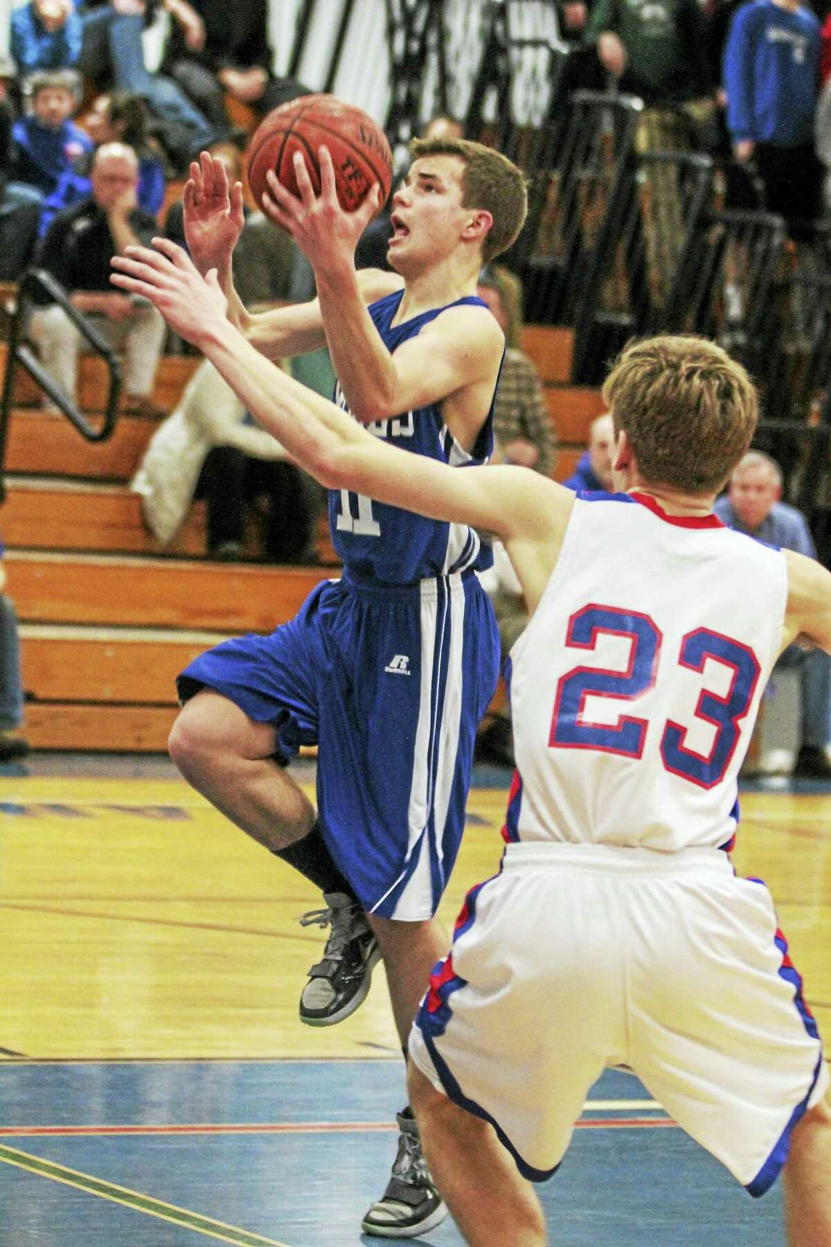 Nonnewaug's Jacob Matta (23) closes in on Lewis Mills' Lorenz Gunzl in a defensive battle for the Berkshire League Boys Basketball early semifinal at Lewis Mills Monday night.