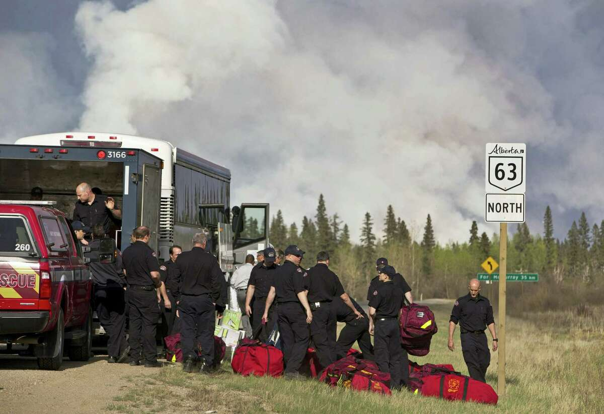 Fire Rescue crews unload in preparation to battle a wildfire in Fort McMurray, Alberta, Thursday, May 5, 2016. An ever-changing, volatile situation is fraying the nerves of residents and officials alike as a massive wildfire continues to bear down on the Fort McMurray area of northern Alberta. The province of Alberta declared a state of emergency.
