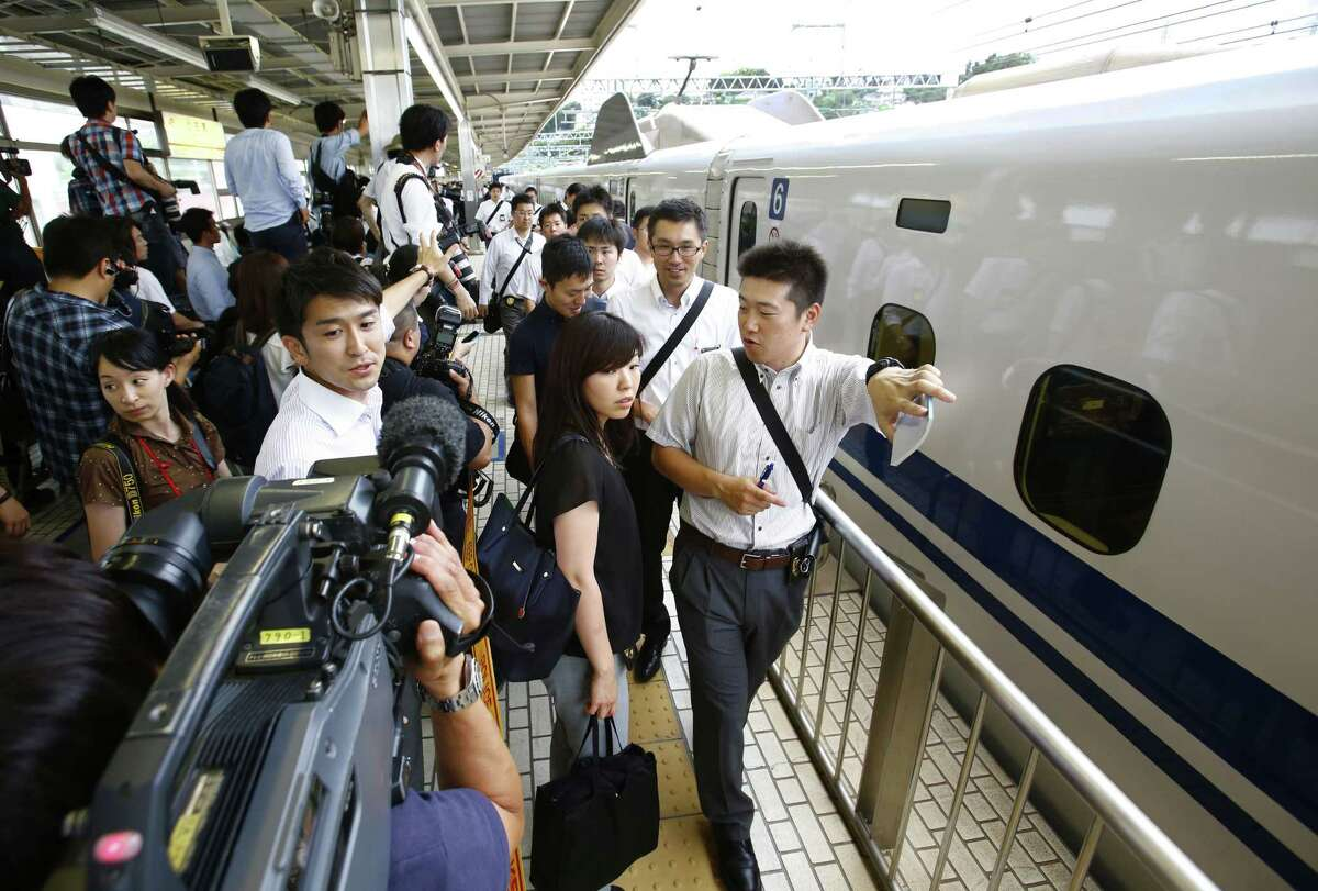 Passengers walk on a platform after getting off a high-speed bullet train where a man set himself of fire, at Odawara station in Odawara, west of Tokyo, Tuesday, June 30, 2015. The man riding the high-speed bullet train set himself on fire Tuesday, killing himself as the coach filled with smoke, Japanese officials and media reports said. (AP Photo/Shizuo Kambayashi)